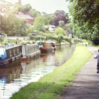 boy riding his bike alongside canals with narrowboat moored